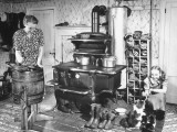 An Old Woman Working in the Old Fashioned Kitchen While the Young Girl Plays with Her Kitten Premium Photographic Print