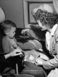 "Stewardess Tempting Little Boy with Model Airplane Aboard the United Airlines ""Nurseryliner"" Premium Photographic Print"