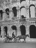 Men Riding in a Horse Carriage, Passing by Ancient Roman Ruins Premium Photographic Print