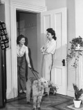 Two Women Talking in the Doorway of a Home, One Holding a Dog by a Leash Premium Photographic Print
