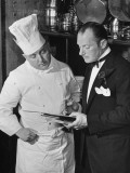 The 21 Club's Jack Kriendler Wearing a Tuxedo and Conferring with a Chef in the Club's Kitchen Fotografiskt tryck