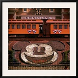 Planted Flowers Forming Design of Mickey Mouse's Face, with Disneyland Train in Background Framed Photographic Print by Loomis Dean