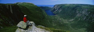 Person Sitting on Cliff, Ten Mile Pond, Gros Morne National Park, Newfoundland and Labrador, Canada Photographic Print by  Panoramic Images
