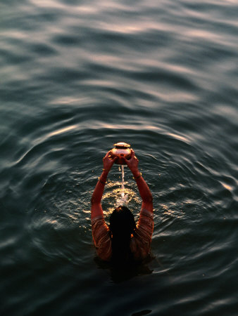 Woman Pouring Water During Morning Puja on Ganges, Varanasi, India Photographic Print by Anthony Plummer