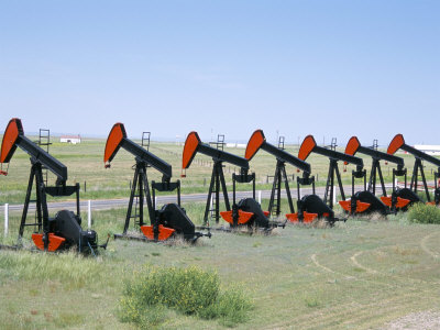 Oil Pumps (Nodding Donkeys) for Sale at Oilfield Supply Merchants, Shelby, Montana, USA Photographic Print by Tony Waltham