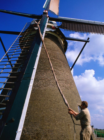 Miller Turning Sails to Stop Windmill in Kinderdijk, Zuid Holland, Netherlands Photographic Print by John Elk III