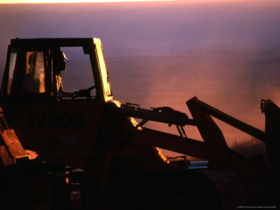 Silhouette of a Man Operating Tractor at Sunset Fotografisk tryk