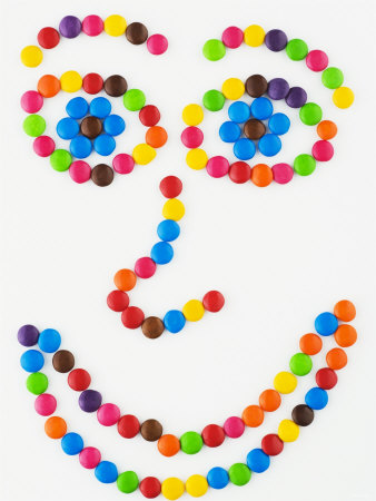 Coloured Chocolate Beans Forming a Smiling Face Photographic Print by Greg Elms