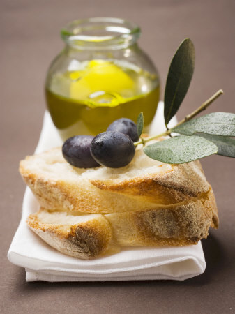 Olive Sprig with Black Olives on White Bread, Olive Oil Behind Fotografisk tryk