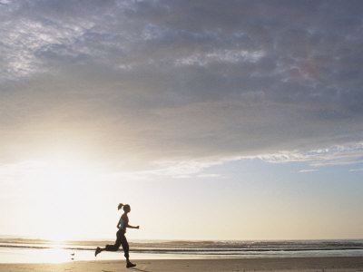 Woman Running on Beach at Sunrise Photographic Print by Kevin Radford