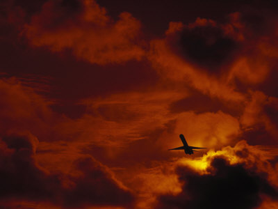 Silhouette of Airplane in Flight at Sunset Photographic Print
