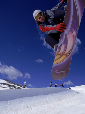 Snowboarder with Colorful Board Doing a Trick Photographic Print by Kurt Olesek