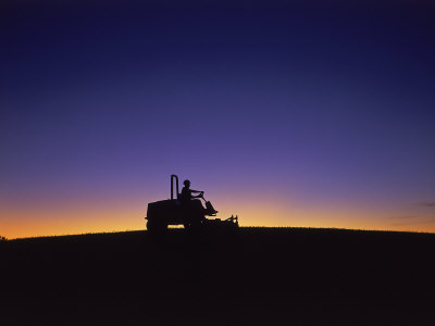 Silhouette of Worker Cutting Grass at Sunrise Photographic Print by Kent Dufault