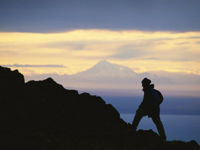 Silhouette of Hiker Ascending Flat Top Mountain at Sunset Photographic Print by Michael Melford