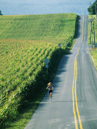 A Woman Jogs Down a Country Road Alongside a Field of Corn Photographic Print by Skip Brown