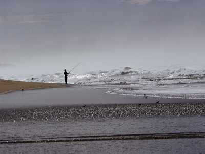 A Fisherman Casts His Line into the Surf Photographic Print by Marc Moritsch