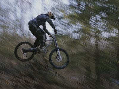 A Boy Flies Through the Air on His Mountain Bike Photographic Print by Roy Gumpel