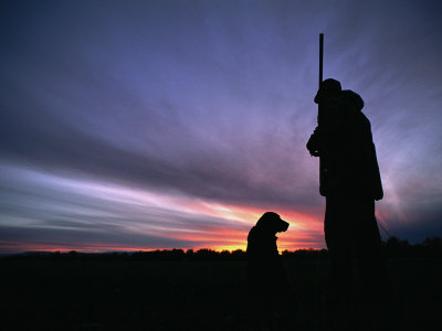A Silhouetted Hunter and His Dog at Twilight Fotografiskt tryck