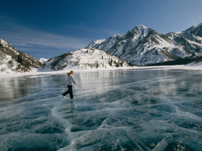 A Girl Ice Skates Across a Frozen Mountain Lake Fotografisk tryk af Michael S. Quinton