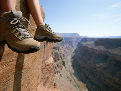 The Boot-Shod Feet of a Hiker Dangle over the Side of a Cliff Photographic Print by John Burcham