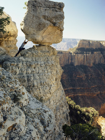 A Man Pretends to Push a Huge Boulder into the Canyon Photographic Print by W. E. Garrett