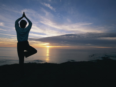 A Woman Practices Yoga on the Beach at Sunset Photographic Print by Roy Toft
