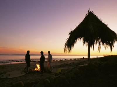 Surfers Stand Near a Fire and Palapa at Hammonds Beach at Sunset Photographic Print by Rich Reid