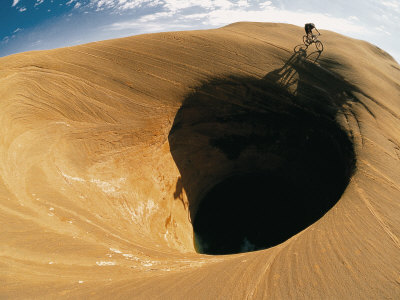 A Mountain Biker Cycles Around a Spectacular Crater in the Desert Fotoprint av Dugald Bremner