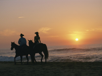 Two People on Horseback Ride Along an Ocean Shoreline at Sunset Photographic Print by Roy Toft