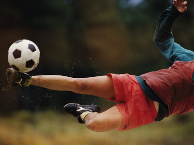 A Man Bends Sideways as He Kicks a Soccerball Photographic Print by Dugald Bremner