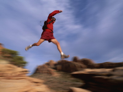 A Runner Leaps Across Rocks in Moab, Utah Photographic Print by Bill Hatcher