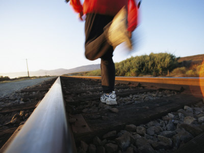 An Athlete Runs on Railroad Tracks Toward the Mountains Photographic Print by Joy Tessman