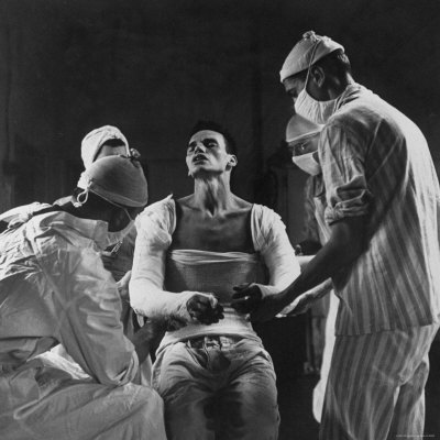 Mortar Wounded Army Medic Private George Lott, Sitting Up While 4 Army Surgeons Finish Up His Cast Photographic Print by Ralph Morse