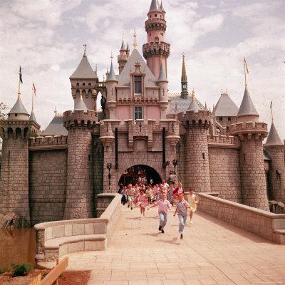 Children Running Through Gate of Sleeping Beauty's Castle at Walt Disney's Theme Park, Disneyland Lámina fotográfica por Allan Grant