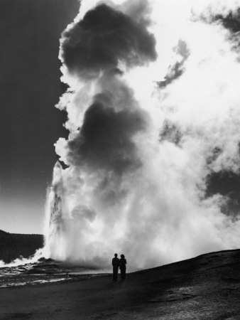 Couple looking at giant water cloud sprouting from Old Faithful Geyser Yellowstone National Park Wyoming USA