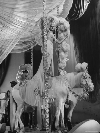 """Chorus Girl Standing on Horse's Back During Filming of the Movie """"The Ziegfeld Follies"""" Photographic Print by John Florea"""