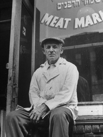 Butcher Taking a Break, Sitting in Front of Meat Market Photographic Print by Ed Clark