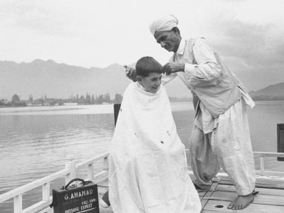 American Tourist, Young Danny Thomas Receiving Hair Cut on House Boat During Vacationing Photographic Print by James Burke