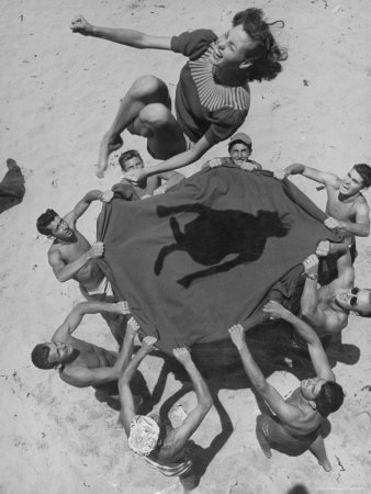 Teenaged Boys Using Blanket to Toss Their Friend, Norma Baker, Into the Air on the Beach Photographic Print by John Florea