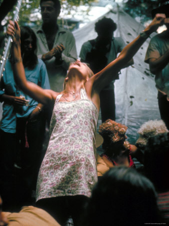 Young Woman with Flute Ecstatically Raising Her Arms, Amid Crowd at Woodstock Music Festival Photographic Print by Bill Eppridge