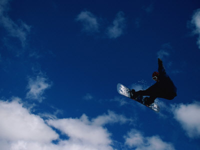A Snowboarder Launches in the Air and Appears for a Second to Be Riding the Clouds Photographic Print by Barry Tessman