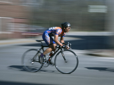 A Bicyclist Speeds Past in a Race Photographic Print by Heather Perry