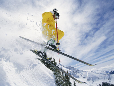 A Skier in a Yellow Suit Goes Airborne Photographic Print by Paul Chesley
