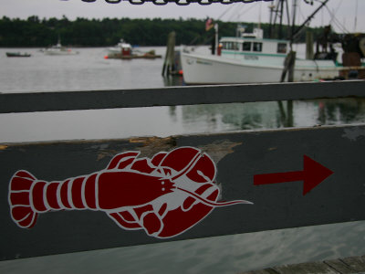 A Lobster Sign Backed by a Lobster Boat on Casco Bay Photographic Print by Stephen St. John