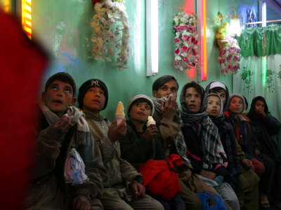 Afghan Boys Watch a Movie on a Television, Unseen, as They Eat Ice Cream at an Ice Cream Shop Fotografiskt tryck