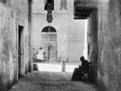 An Alley of Rome Where a Woman Sitting on a Chair is Working at a Piece of Crocheting Photographic Print