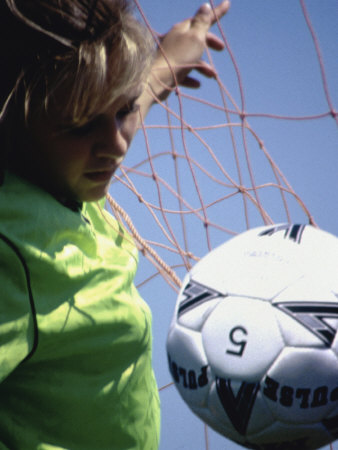 Girl Standing in a Goal Looking at a Soccer Ball Photographic Print