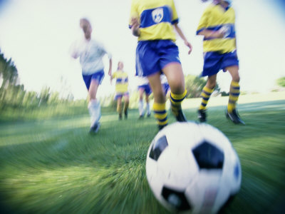 Low Angle View of a Girls Soccer Team Playing Soccer on a Field Photographic Print