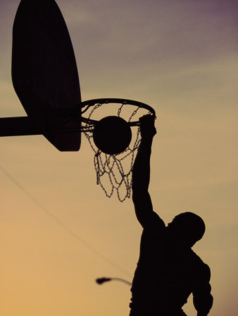Silhouette of a Man Slam Dunking a Basketball Photographie