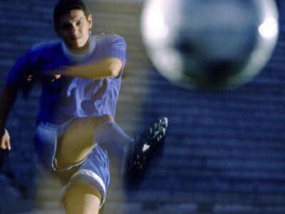 Soccer Player Kicking a Soccer Ball Photographic Print